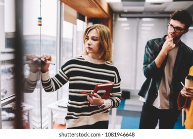 Female professional teacher with textbook in hand eaxplaining productive stratedy to student drawing successful scheme during training session in university.Pensive coach writing plan for employees