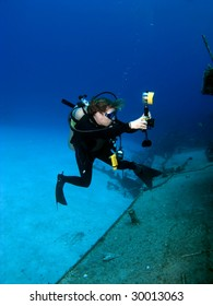 A Female Professional Underwater Photographer shooting the MV Tibbetts in Cayman Brac