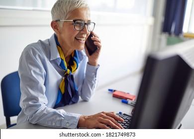 Female professor enjoying smartphone call in the lecture break