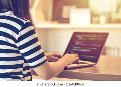 A female programmer typing source codes in a modern loft creative office. Studying, Working, Technology, Freelance Work Concept. Shallow focus.