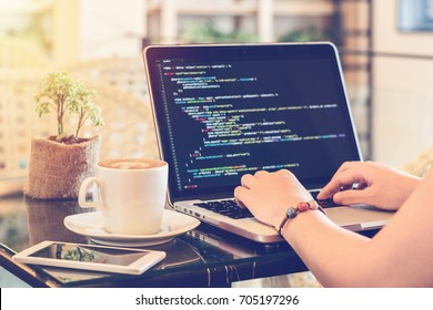 A female programmer typing source codes in a coffee shop with a relaxing working environment. Studying, Working, Technology, Freelance Work, Web Design Business, and Web Development Concept.