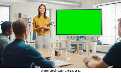 Female Project Manager Holds Meeting Presentation for a Team of Developers. She Shows Green Screen Interactive Whiteboard Device for Business Planning Concept. Young People Work in Creative Office.