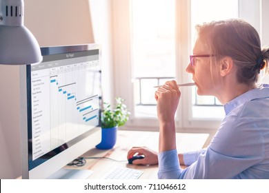 Female project manager using Gantt chart schedule to organize tasks and update planning on computer screen with software