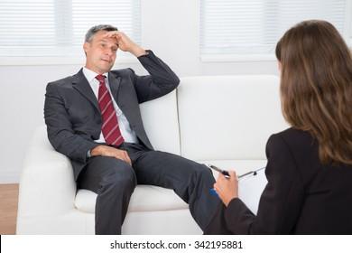 Female Psychiatrist Listening About Problem Of Depressed Patient