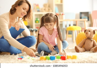 Female psychologist with cute little girl during play therapy