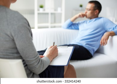 Female psychologist making notes while consulting man