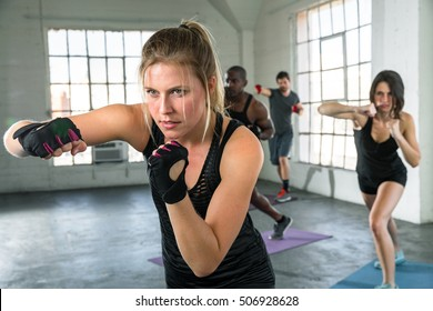 Female punching in aerobics fitness high intense fitness class coed unisex group lifestyle