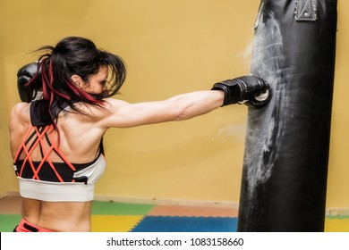 Female Punching A Bag With Boxing Gloves On yellow background