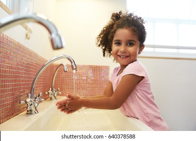 Female Pupil At Montessori School Washing Hands In Washroom
