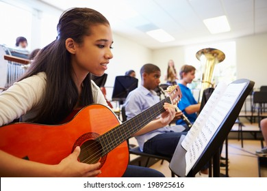 Female Pupil Playing Guitar In High School Orchestra