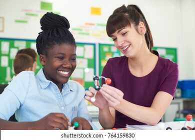 Female Pupil And Teacher Using Molecular Model Kit In Science Lesson