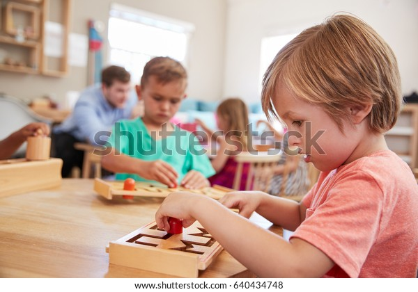 Female Pupil Working At Table In Montessori School