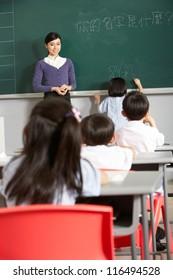 Female Pupil Writing On Blackboard In Chinese School Classroom