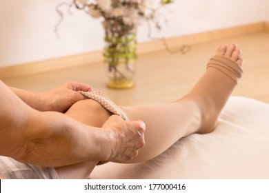 Female puts some anti-thrombotic stockings on