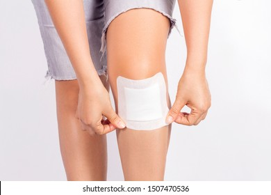 Female putting adhesive plaster wound sealed on khee on white background