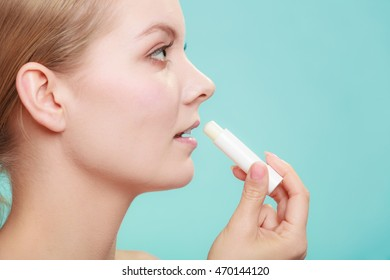 Female putting applying lip balm moisturizing balsam. Girl taking care of lips. Skincare.