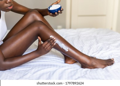 female putting Moisturizer on her legs at home