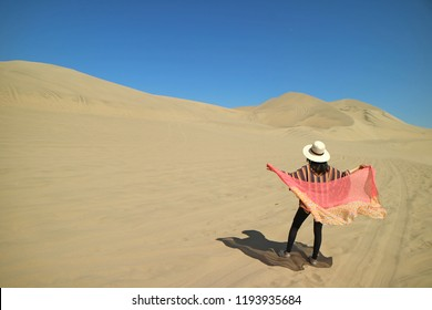 Female putting on her scarf on the windy day at Huacachina desert in Ica region of Peru, South America
