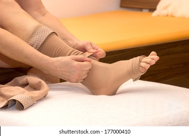 Female putting thrombosis stockings on