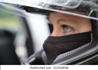 Female race car driver wearing helmet and balaclava