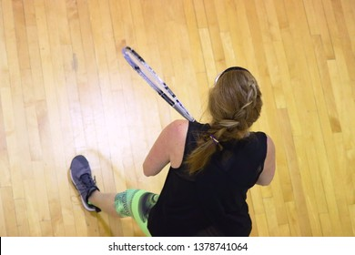 Female racquetball player on wood flooring