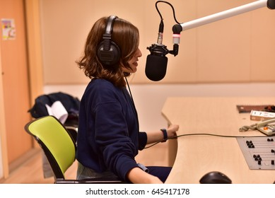 female radio host working in front of a microphone on the radio station
