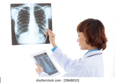 Female radiologist comparing chest x-ray with an image on the digital tablet