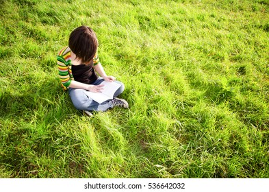 Female reading a book whilst sitting on the grass. Shallow depth of field, blur, soft focus and overexposure used for effect.