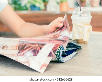 Female reading a magazine and drink ice coffee on wooden table.