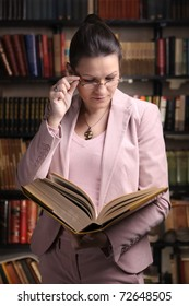 Female reading a thick old book in front of colorful bookshelf
