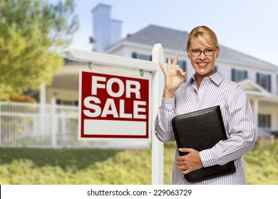 Female Real Estate Agent in Front of Home For Sale Sign and House.