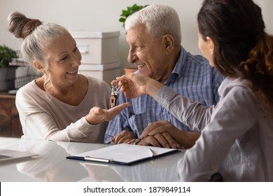 Female real estate agent give keys to new home to excited elderly couple clients. Woman realtor or broker congratulate happy overjoyed mature spouses with house purchase. Ownership concept.