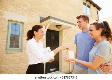 Female real estate agent giving keys to new property owners