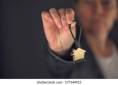 Female real estate agent with house model key ring, selective focus