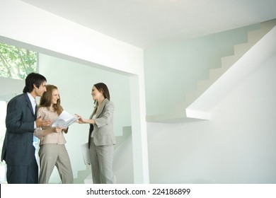 Female real estate agent showing house to young couple, pointing to blueprints