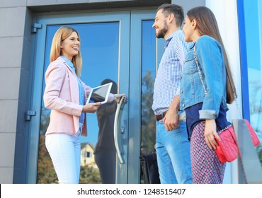 Female real estate agent welcoming couple to show house, outdoors