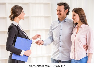 Female realtor is giving to young couple a key from new flat.