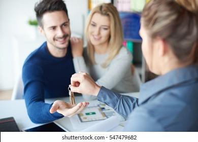 Female realtor handing keyring to man
