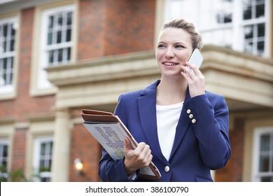Female Realtor On Phone Outside Residential Property