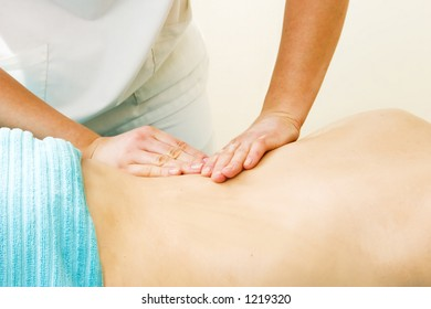 A female receives a lower back massage at a day spa.
