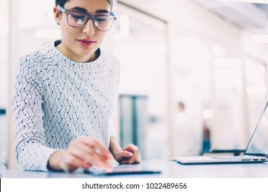 Female receptionist checking notification on digital gadget creating schedule and organizing work,woman administrative manager in eyewear reading income message standing at clinic near publicity area