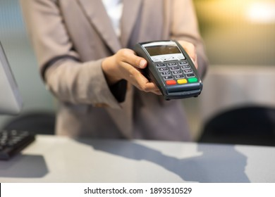 Female receptionist employee holding card reader machine on hand at checkout counter.