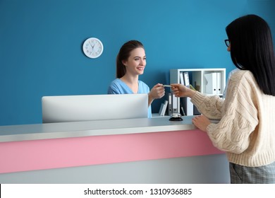 Female receptionist receiving payment for medical service from patient in clinic