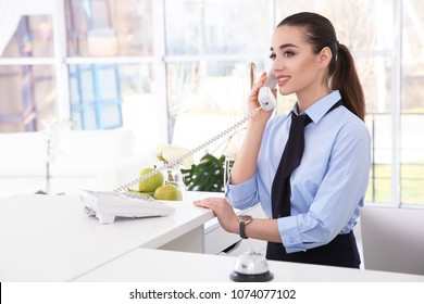 Female receptionist talking on phone at workplace in hotel