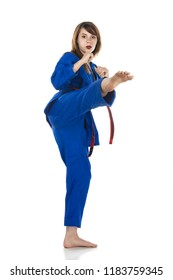 Female red belt student practicing Tae Kwon Do martial arts moves in a blue dobok or gi (uniform) isolated on white.