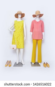 Female red clothing with sundress and yellow trousers ,straw hat, handbag on two mannequin isolated