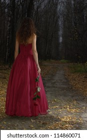 Female in red dress walking in the autumn forest