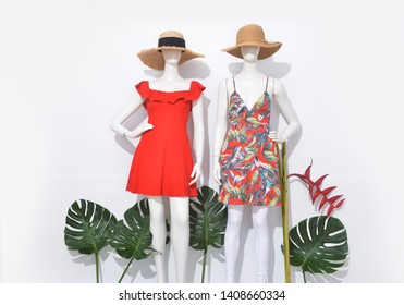 Female in red and floral .palm pattern sundress,hat on two mannequin isolated with monstera and  bird of paradise