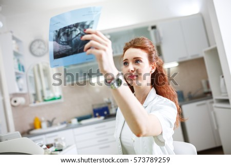 Female red hair dentist in dental office examining x-ray image.