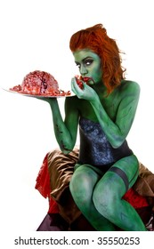 Female, red hair, zombie body paint, green skin, lingerie, white background, red chair,  orange heels, sitting, adult, 3/4 body, eating brains